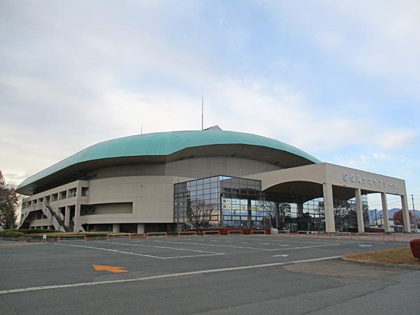 タカヤアリーナの外観。屋根が緑でなだらかな丸みを帯びている。建物の前には駐車場がある。