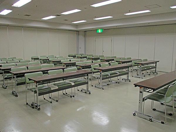 会議室の様子。長机が並んでいて、1つの長机に椅子が3脚備え付けられている。